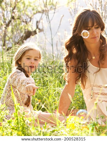 Beautiful mother and young daughter sitting in a golden green field with trees, grass and flowers, playing with floating bubbles during a holiday vacation outdoors. Family activities lifestyle. - stock photo