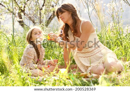 Beautiful mother and young daughter sitting in a golden green field with trees, grass and flowers, playing to blow floating bubbles during a holiday vacation outdoors. Family activities lifestyle. - stock photo