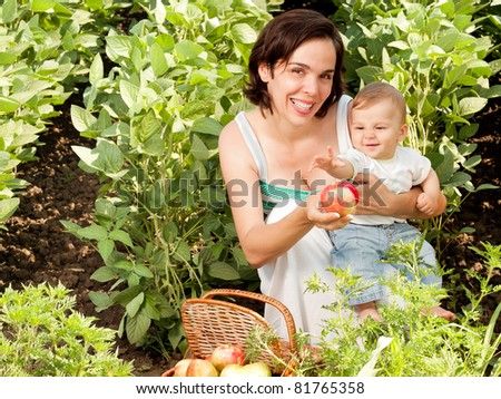 Beautiful mother ans baby son smiling portrait outdoors - stock photo