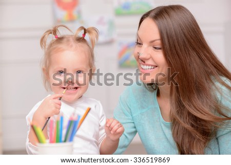Beautiful mother are her daughter are making fun at home. They have paint on their faces. The lady and girl are smiling - stock photo