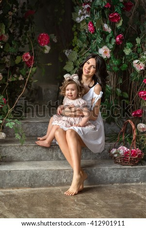 beautiful mother brunette in white sundress holding in her arms little girl sitting in the garden of rose bushes - stock photo