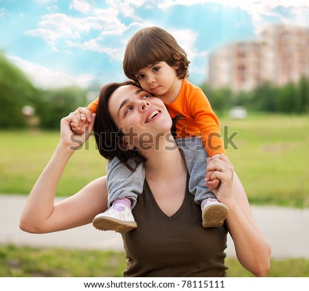 Beautiful mother carrying little daughter - stock photo