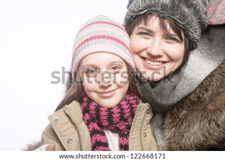 beautiful mother daughter winter portrait, studio shot - stock photo