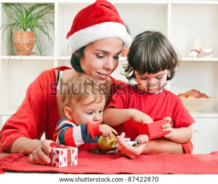 Beautiful mother embracing her little children and opening Christmas presents - stock photo