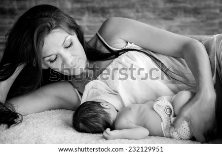 beautiful mother feeding her newborn with breast  ( black and white ) - stock photo