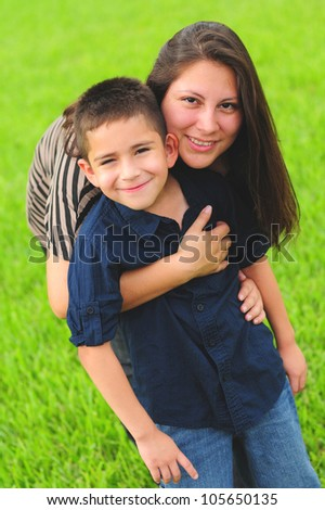 Beautiful mother hugging son outdoors in summer - stock photo