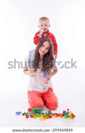 Beautiful mother is playing with her child. She is holding her son on her shoulders. They are smiling and looking at the camera with happiness. Isolated on background - stock photo