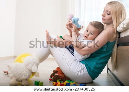 Beautiful mother is sitting on flooring and holding her small son. She is hugging him with love. The boy is holding a toy and looking at the camera with interest  - stock photo
