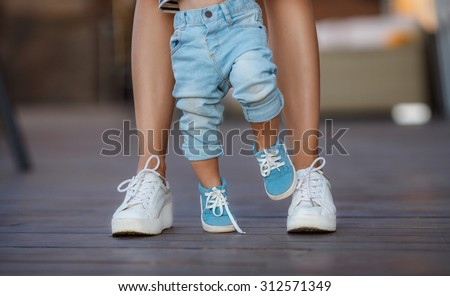beautiful mother is walking on the pier with her little baby boy son with first steps. feet of mother and child - stock photo