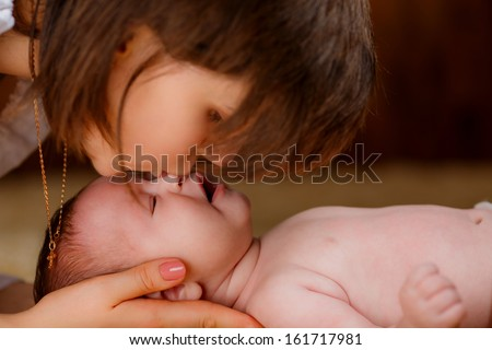 beautiful mother kisses her newborn baby's nose - stock photo