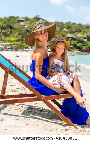 Beautiful mother lady in blue dress and beach straw hat with her pretty blonde cute daughter. Woman in a beach chair and little girl smile to the camera. Happy family on the shore. Happy mothers day. - stock photo