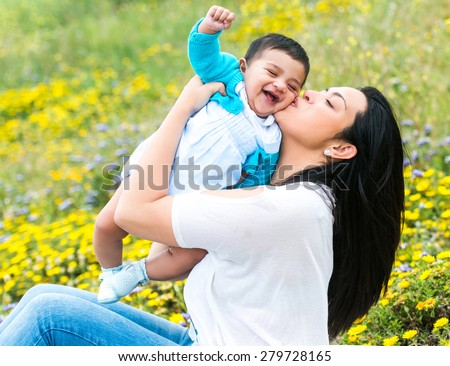 beautiful mother playing with her baby boy on the meadow in summer day - stock photo