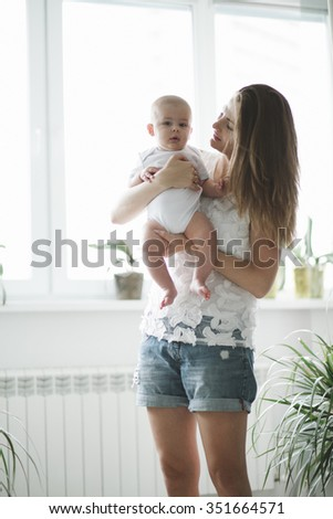 Beautiful mother portrait playing with her cute little boy - stock photo