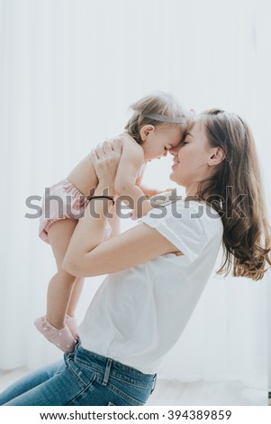 Beautiful mother portrait playing with her cute little girl in a white room - stock photo
