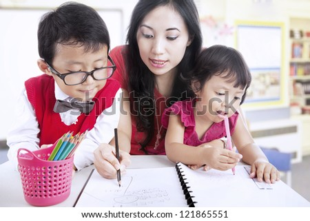 Beautiful mother teaches her children to write in class