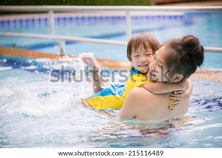 Beautiful mother teaching cute little boy how to swim in a swimming pool. Child having fun in water with mom - stock photo