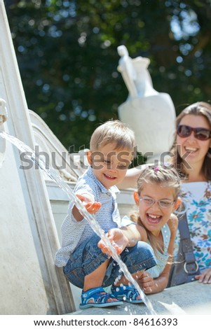 Beautiful Mother with her kids playing with water in fountain. Vertical view - stock photo