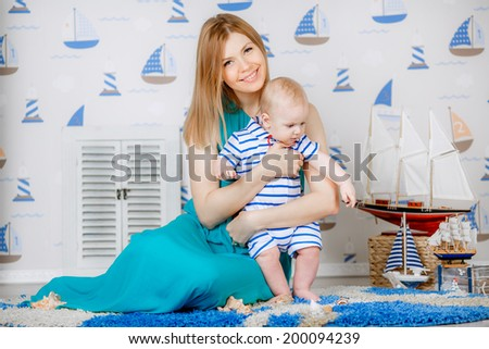beautiful mother with her son in the studio. nautical theme - stock photo