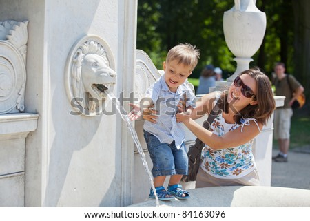 Beautiful Mother with her son playing with water in fountain - stock photo