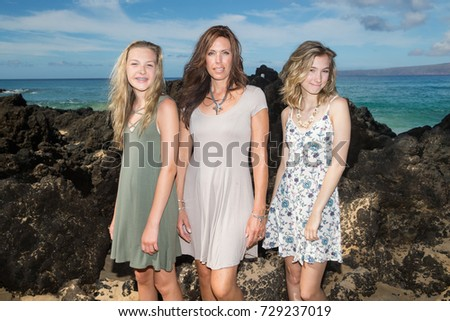Beautiful Mother with her two daughters at a beach