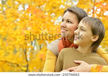 Beautiful mother with son in autumn park - stock photo