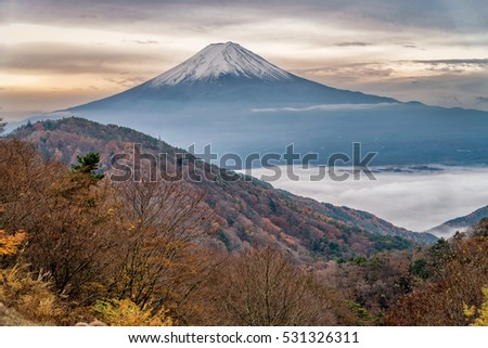 Beautiful mount Fuji in autumn color season of trees. The Kawaguchi town and lake below covered with sea of fog.