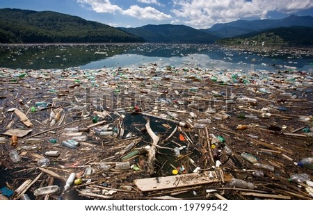 beautiful mountain and lake landscape ruined by heavy trash pollution - stock photo