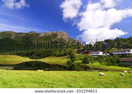 beautiful mountain green landscape with sheep and farm - stock photo