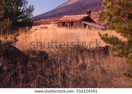 Beautiful mountain hut in Sicily, Italy; Etna volcano on background.