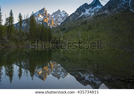 Beautiful mountain lake reflection of rugged rocky Teton snow capped mountain range blue sky majestic landscape scene  - stock photo