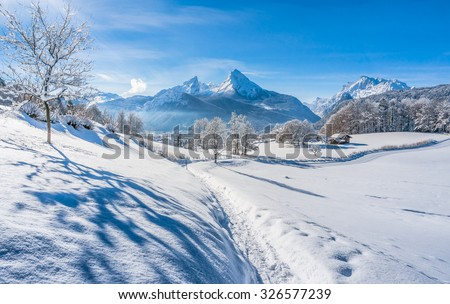 Beautiful mountain landscape in the Bavarian Alps with a snowy path down to the village of Berchtesgaden and famous Watzmann massif on a sunny day, Nationalpark Berchtesgadener Land, Bavaria, Germany - stock photo