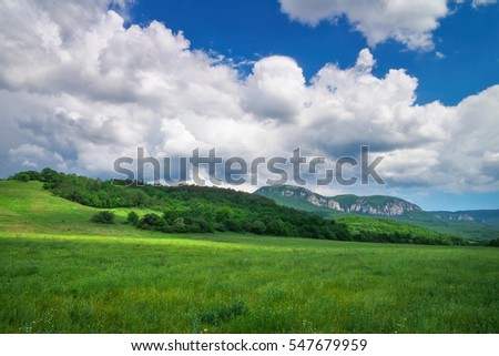 Beautiful mountain landscape with field and cloudy sky.