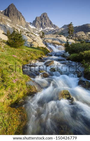 Beautiful mountain range with river flowing in the foreground - stock photo