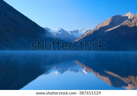 Beautiful mountain range with snow on the peak are reflected in foggy lake - stock photo