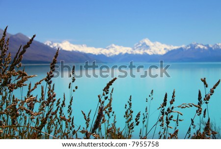 Beautiful mountain turquoise color lake, blue sky and snow peaks reflecting in the water. Lake Tekapo, Mount Cook National Park, New Zealand - stock photo