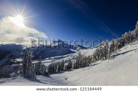 Beautiful mountains and sun during wintertime - stock photo