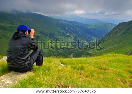Beautiful mountains landscape with lake and clouds in Carpathian mountains and man with binoculars - stock photo