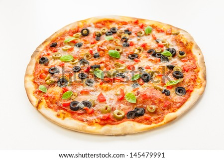 Beautiful multi colored and crispy pizza with basil, melted cheese and salami slowly turning on rotating table with white background - stock photo