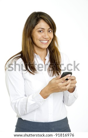 Beautiful multi-racial young woman in business attire portrait smiling at viewer as she texts on cellular or smart phone. Full length portrait against white background