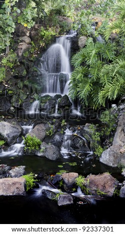 Beautiful multi-tiered waterfall over rocks through lush tropical vegetation. - stock photo