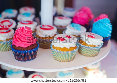 Beautiful multicolored decorated baked sweet tasty cupcake cupcakes with buttercream on a party with happy people around  - stock photo