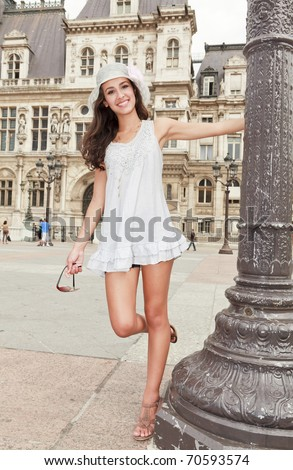 Beautiful multicultural young woman in a fashion pose in a typical Paris plaza with historical architecture in the background. - stock photo