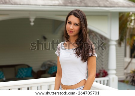 Beautiful multicultural young woman outdoor portrait in a home setting. - stock photo