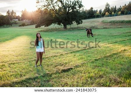 Beautiful multicultural young woman outdoor portrait on farm in horse field - stock photo
