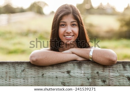 Beautiful multicultural young woman outdoor portrait on farm next to fence with sun behind - stock photo