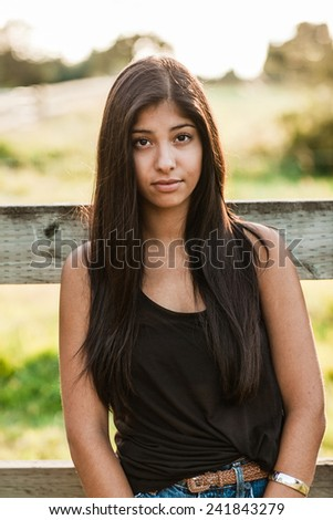 Beautiful multicultural young woman outdoor portrait on farm next to fence with sun behind