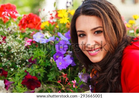 Beautiful multicultural young woman outdoor portrait with colorful flowers in the background. - stock photo