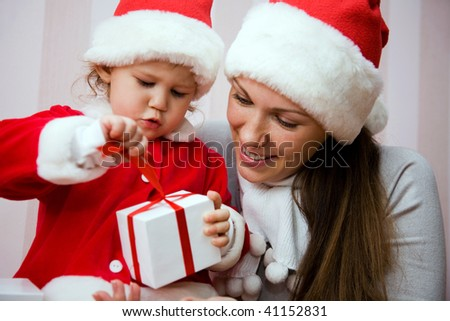 Beautiful mum with a small child open a Christmas gift