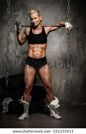 Beautiful muscular bodybuilder woman standing near stack of  tyres with hammer on her shoulders - stock photo