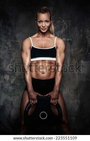 Beautiful muscular bodybuilder woman with weights  - stock photo